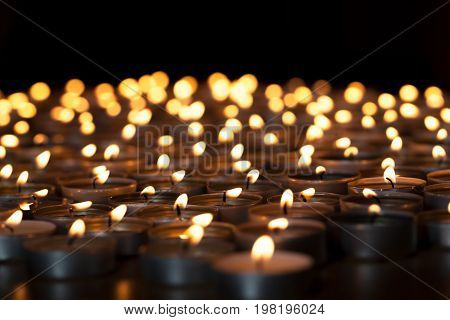 Flaming candles. Spiritual image of tealights providing sacred light. Romantic candlelight at night. A spread of lit wax candles against black background with copy space.