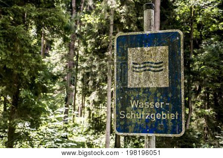 old rusty vintage forgotten german sign in the forest translation wasser schutzgebiet means water reserve