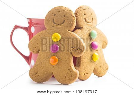 Two gingerbread men leaning against a cup. Xmas gingerbread.