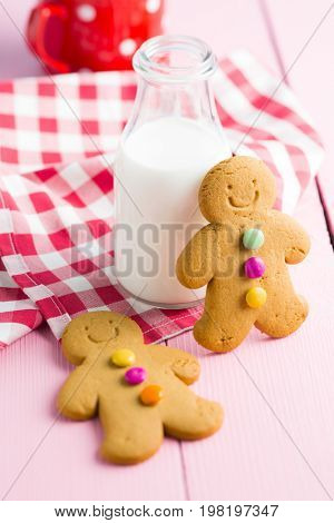 Sweet gingerbread man and milk bottle on pink table. Xmas gingerbread.