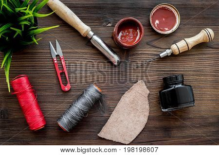 Leather craft workshop. Tools on dark wooden table background top view.