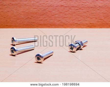 Nut and screws for reliable fastening small tools for repair on a wooden background