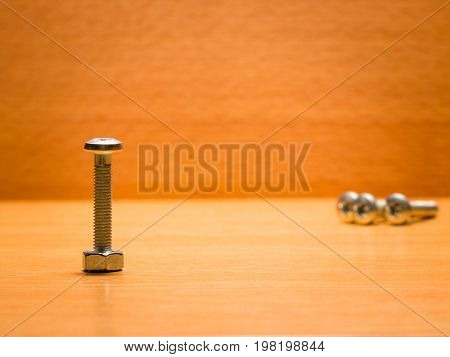 Screws and nut necessary tools for your home are durable and reliable on a wooden background used for fastening