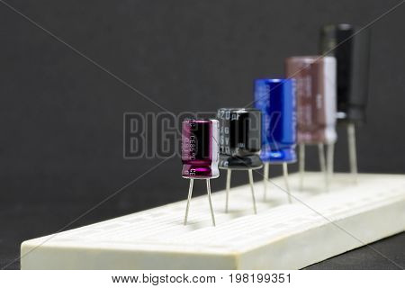 Electrolytic Capacitors installed in pcb circuit board multi color and many sizes on black background Electronics part concept.