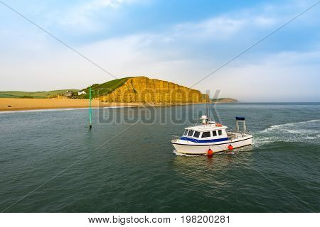 Fishing boat returns to harbour at West Bay in Dorset