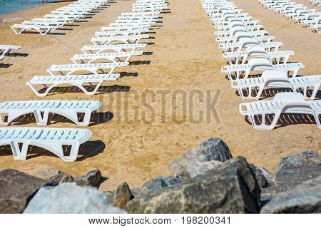 White sunbed on the sand beach at the sea summer sea rest concept.