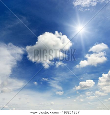 Bright sun and clouds on  background epic dark blue sky.