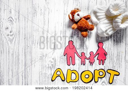 Adopt word, paper silhouette of family and toys on light wooden table background top view.