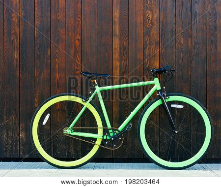 Bright green Fixed Gear beautiful vintage bicycle stands in a black wooden wall. Hipster.