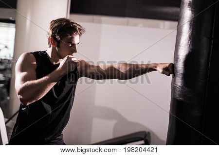 Young Athlete Working Out By Throwing Punches At A Heavy Punching Bag In Gym. Training