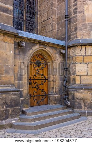 Wooden entrance door to the medieval temple, St. Vitus Cathedral, Prague, Czech Republic