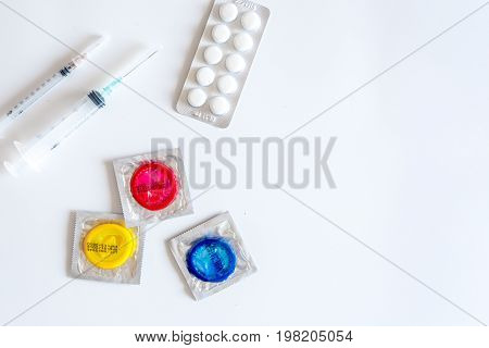 Visit the urologist. Syringes, pills and condoms on white background top view.