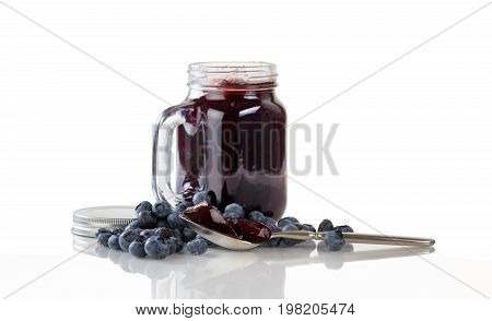 Blueberry jam in spoon with fresh ripe blueberries and jar in background. Isolated on white with reflection.