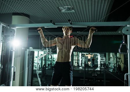 Very Power Athletic Guy , Execute Exercise Tightening On Horizontal Bar, In Sport-hall