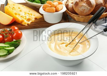 Cheese fondue in plate with different products on white table