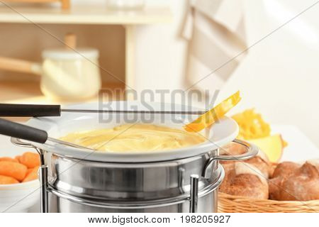 Stick with piece of bell pepper and cheese fondue in pot, closeup