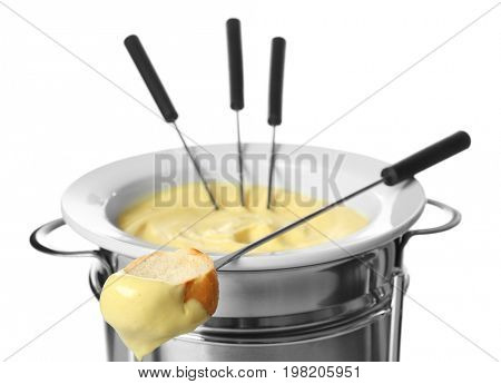 Cheese fondue in pot and piece of bread on stick against white background