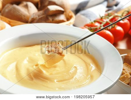 Dipping stick with piece of bread into cheese fondue, closeup
