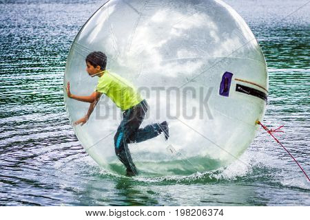 Aquazorbing. Aqua zorbing on water. Playing boy