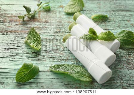 Hygienic lipsticks with lemon balm on wooden background