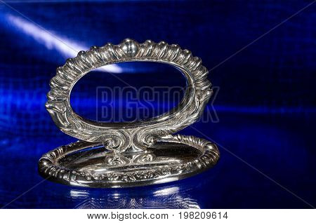 Ornate Antique Silver Paperweight Resting on a Blue Surface