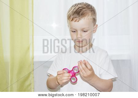 Popular fidget spinner in hand of little boy. Child hand holding popular fidget spinner toy