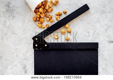 Watching film. Clapperboard and popcorn on grey stone background top view.