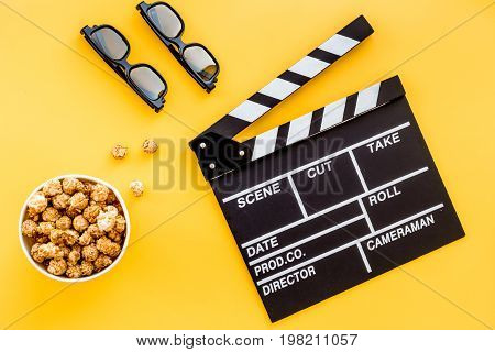 Watching film. Clapperboard, glasses and popcorn on yellow background top view.