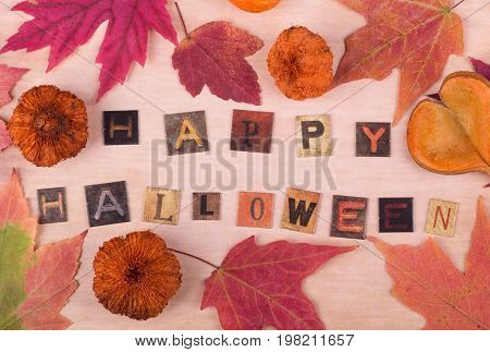 Happy halloween text with autumn leaves and objects on vintage surface