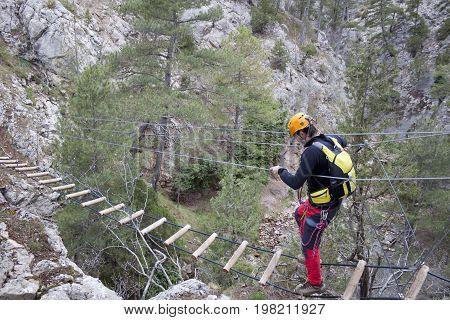 Mountaineer Crossing A Bridge Of A Via Ferrata