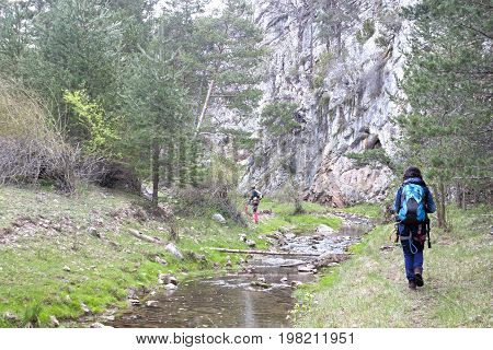 Two Walkers Close To The River In The Mountains