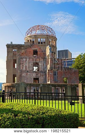 Atomic bomb dome in Hiroshima Japan on a sunny day with blue sky and green grass. First A-bomb was dropped in Hiroshima this ruin was left standing.