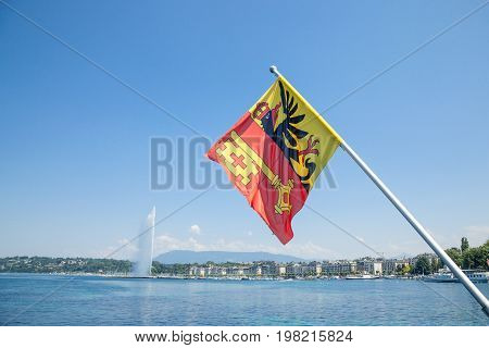 Flag of the Geneva Canton in the city center of Geneva on the Leman lake. The iconic Jet d'Eau (Water Jet) can be seen in the background