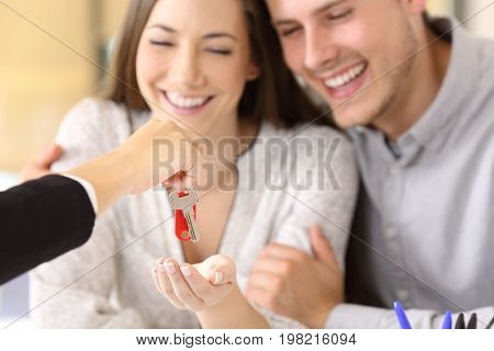 Close up of a happy homeowners receiving their new house keys from a real estate agent at office