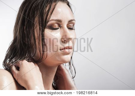 Beauty Concepts and Ideas. Portrait of Caucasian Sensual Brunette with Closed Eyes Showing Wet and Shining Skin and Wet Hair. Creative Makeup. against Grey. Horizontal Image Orientation
