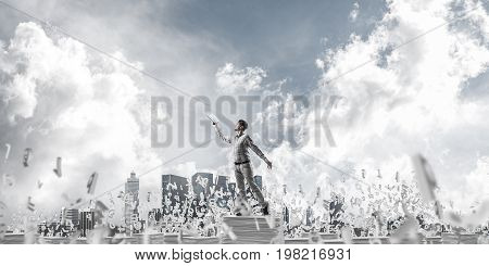 Man in casual wear keeping hand with book up while standing among flying letters with cloudly sky on background. 3D rendering.