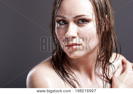 Portrait of Sensual Tanned Caucasian Brunette Woman With Sad Expression with Wet and Shining Skin and Wet Hair. Against Dark Grey Background.Horizontal Image Orientation