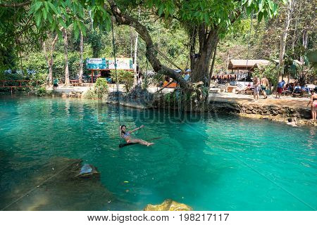 VANG VIENG LAOS - MARCH 14 2017: Black hair girl playing at the swing in Blue Lagoon located close to the city of Vang Vieng Laos.