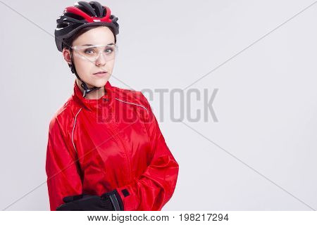 Sport Concepts and Ideas. Portrait of Caucasian Female Cycling Athlete Posing Equipped in Professional Outfit in Studio. Horizontal Image