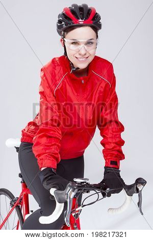 Cycling Concepts. Portrait of Caucasian Female Cyclist Equipped in Cycling Outfit and Posing With Road Bike In Studio. Vertical Shot