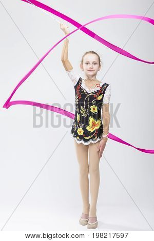 Sport Concepts. Little Caucasian Female Rhythmic Gymnast In Professional Competitive Suit Doing Artistic Ribbon Spirals Exercises in Studio On White. Vertical Shot