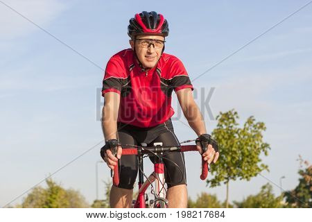 Cycling Concepts. Smiling Caucasian Road Cyclist During Ride on Bike Outdoors. Completely Equipped in Professional Outfit.Horizontal Image Composition