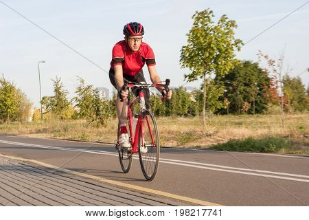 Sport and Cycling Concepts. Professional Male Cyclist in Racing Outfit During a Ride on Bike Outdoors. Horizontal Image Composition