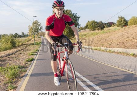 Portrait of Professional Caucasian Male Road Cyclist Having His Training Outdoors. Going Uphill. Horizontal Image Composition