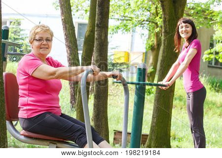 Elderly senior and young woman in sports wear exercising upper and lower body on outdoor gym in park sporty lifestyles and slimming concept