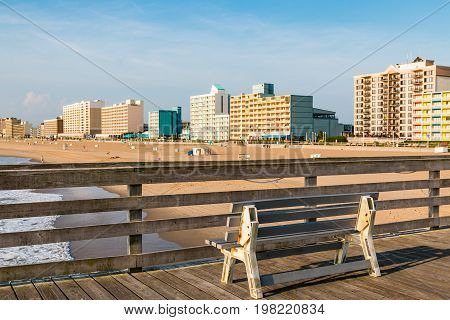 VIRGINIA BEACH, VIRGINIA - JULY 13, 2017:  A bench sits on the fishing pier at daybreak with a view of the oceanfront hotels in the background.
