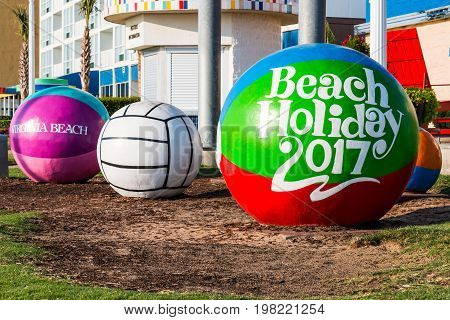 VIRGINIA BEACH, VIRGINIA - JULY 13, 2017:  Colorful concrete beach balls sculpture by Larson Design Group on the oceanfront boardwalk and created in 1993.