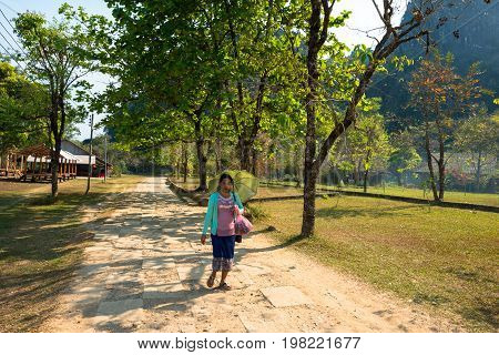 VANG VIENG LAOS - MARCH 14 2017: Local Lao woman walking with umbrella at the Nam Song River close to the city of Vang Vieng Laos.