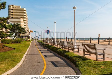 VIRGINIA BEACH, VIRGINIA - JULY 13, 2017:  The oceanfront boardwalk for pedestrians with a parallel paved path for bikes and surreys.