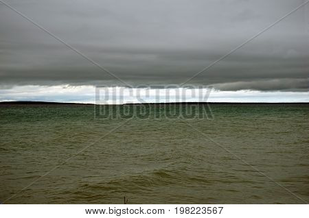A view of the Straits of Mackinac, including Round Island and Bois Blanc Island, as seen from Alexander Henry Park in Mackinaw City, Michigan, during a cloudy day in June.
